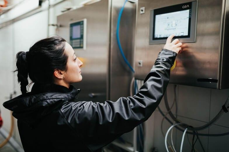 En dame som programmerer en maskin